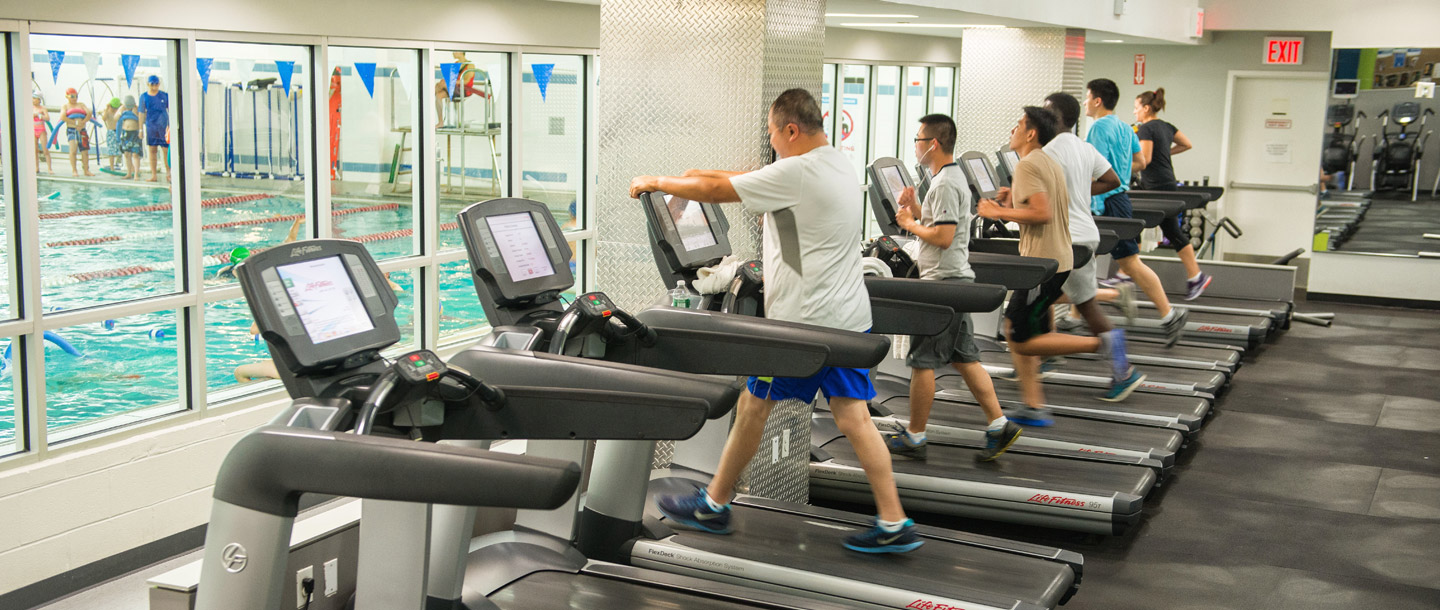 People working out on treadmills at Chinatown YMCA overlooking indoor pool
