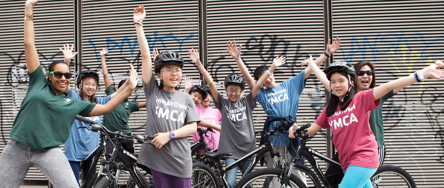 Group of girls on bikes with arms up with YMCA shirts