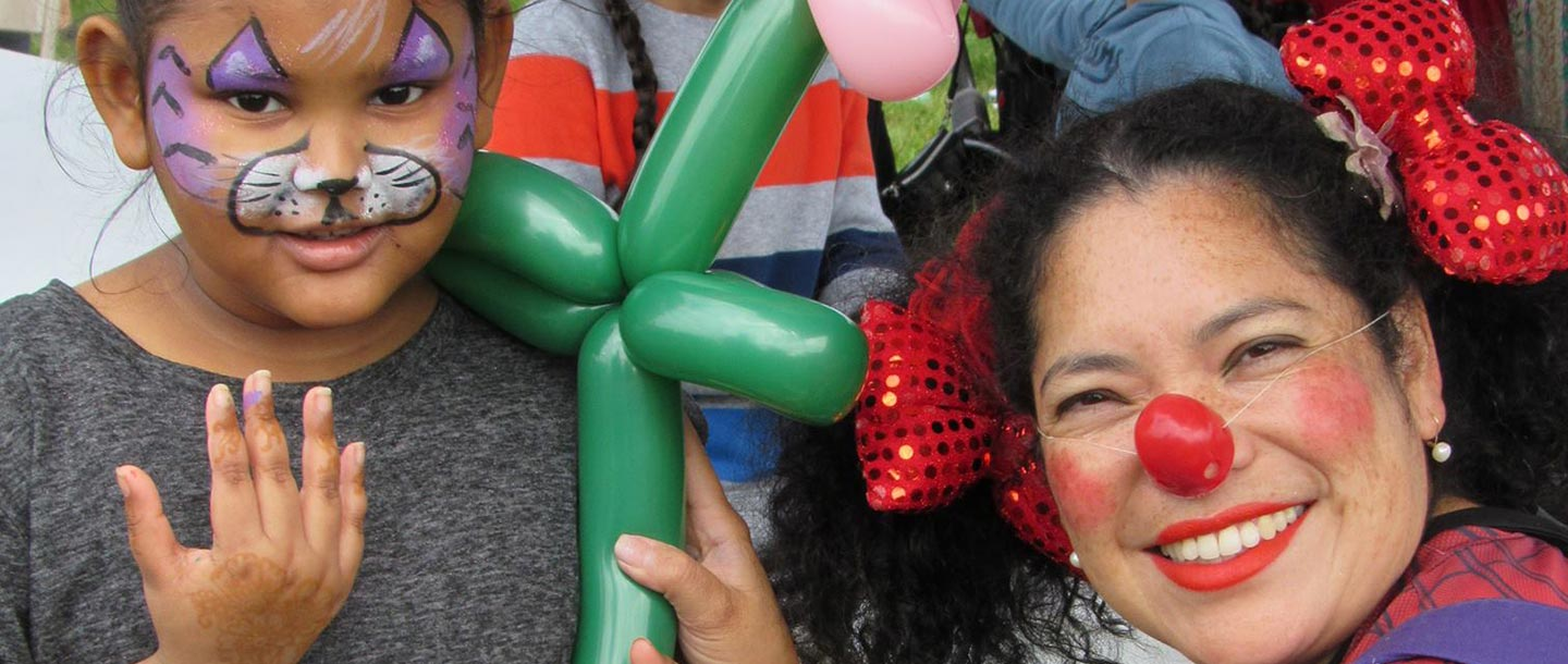 Little girl with balloon art and facepaint with clown at free YMCA family event