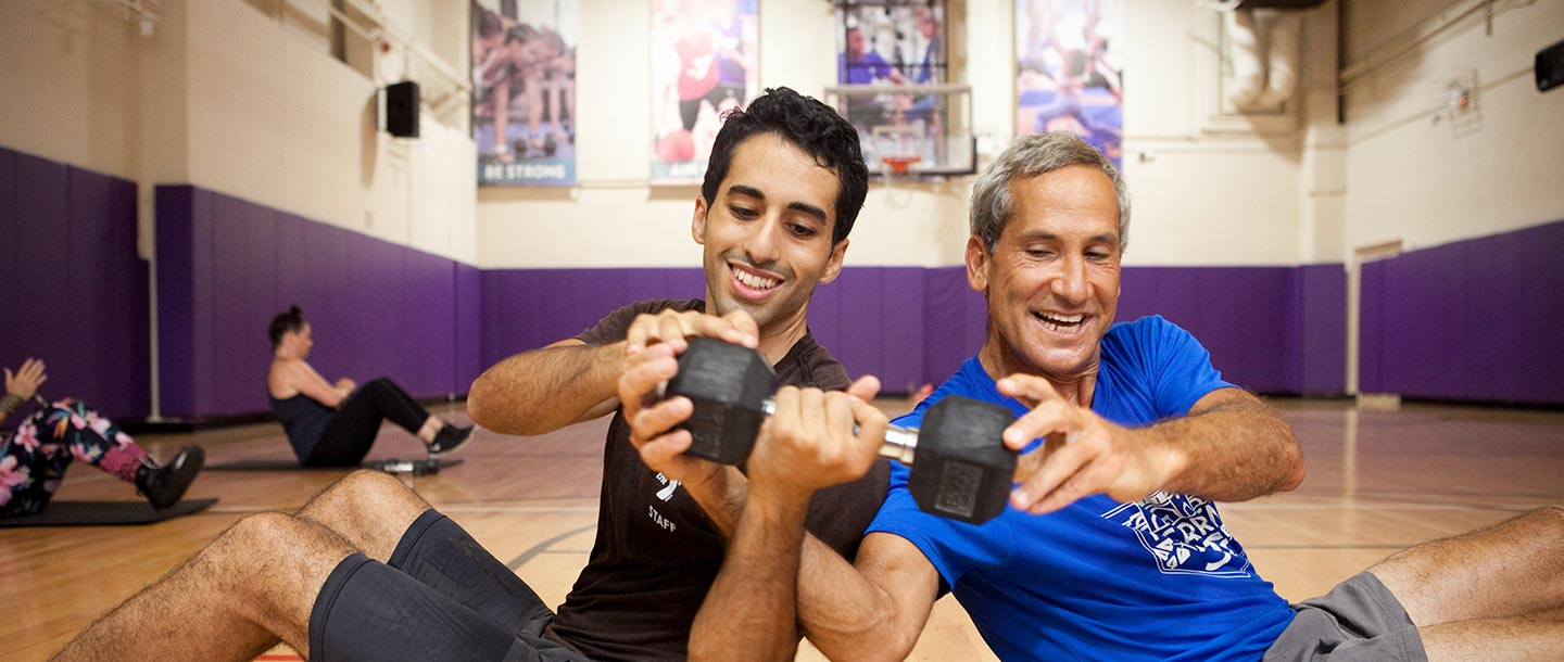 Two men passing weight to each other at Brooklyn YMCA group fitness class