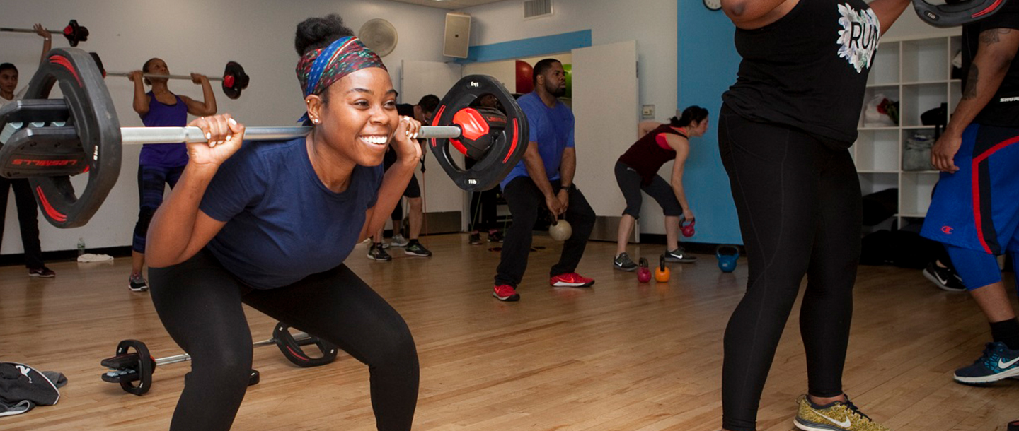 Woman lifts weights in group fitness class at the YMCA