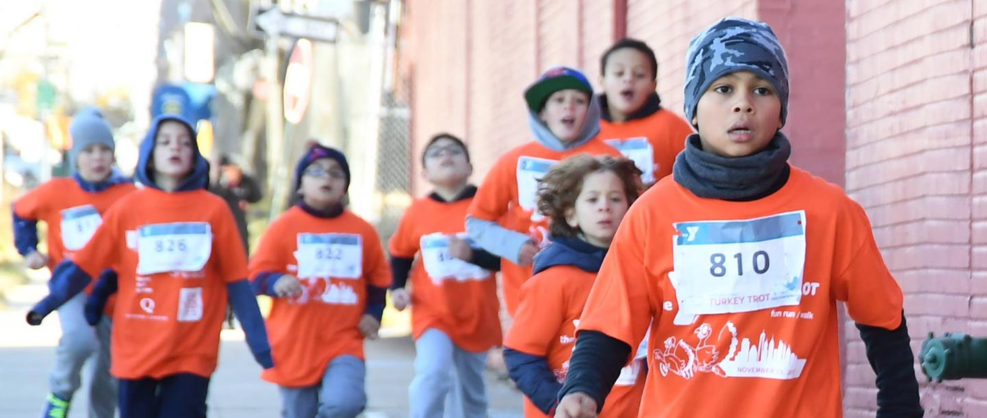Group of children in orange t-shirts running during YMCA fun run event for families