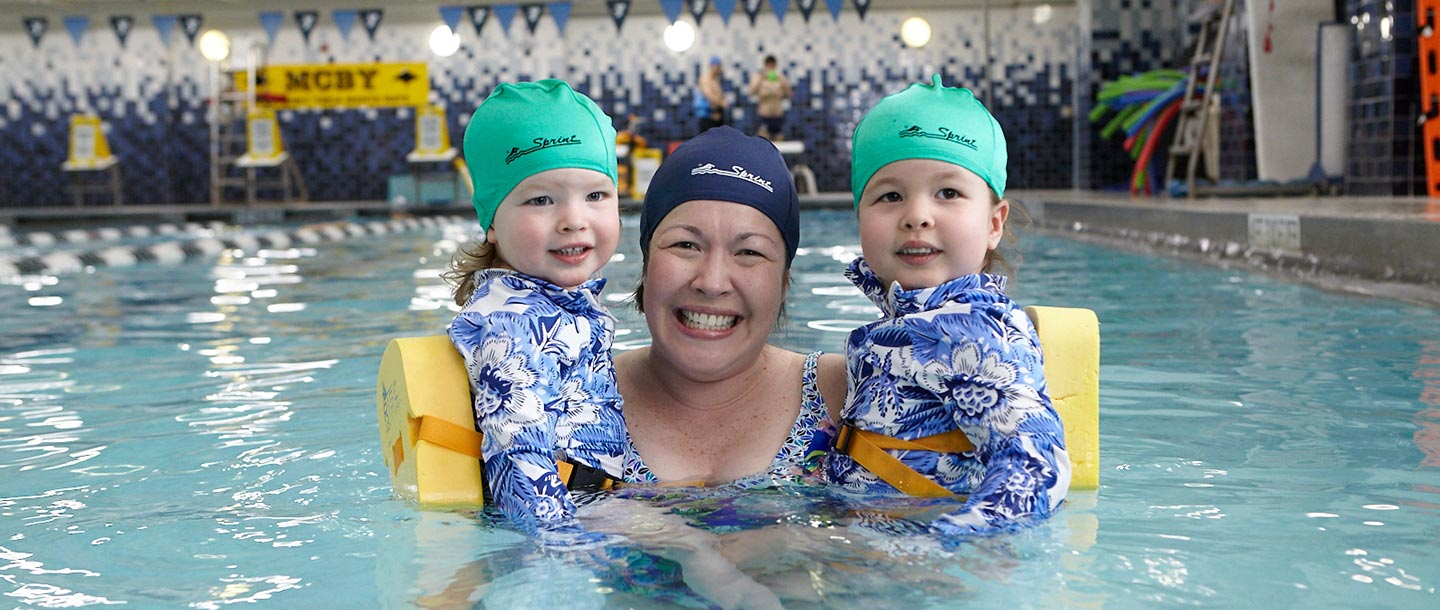 Mom holds two toddler daughters in McBurney YMCA indoor pool