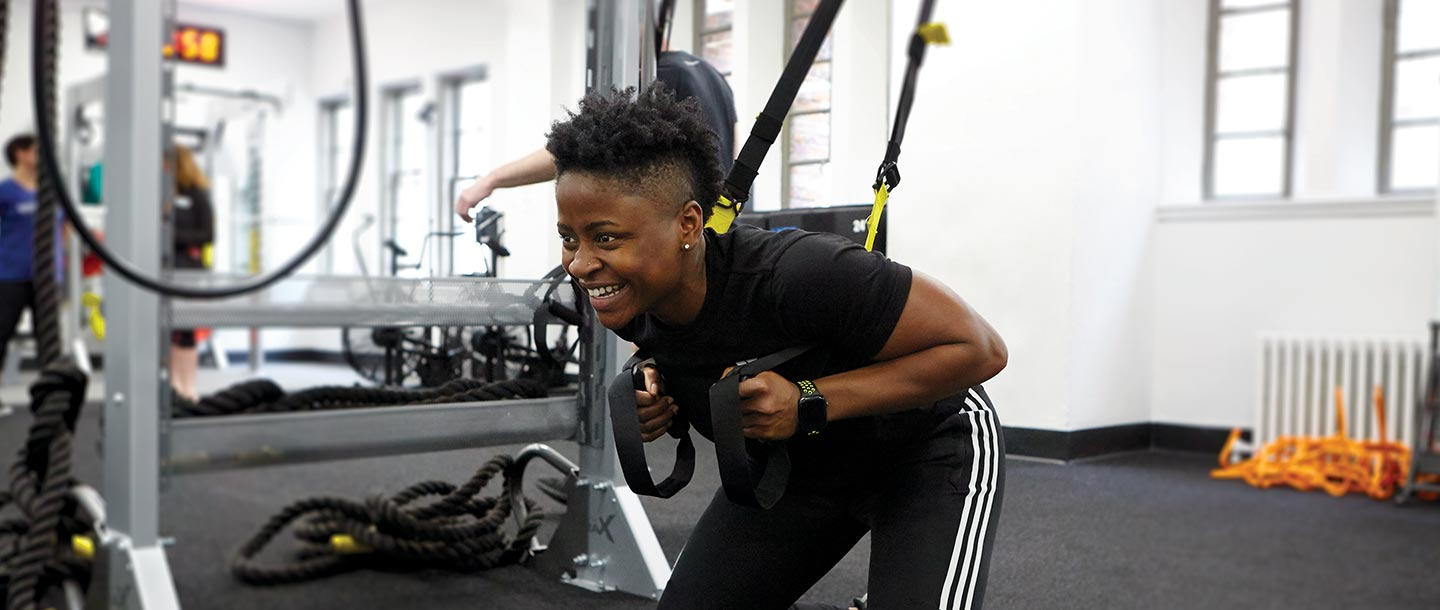YMCA instructor demonstrates how to squat with TRX equipment during fitness class at YMCA gym