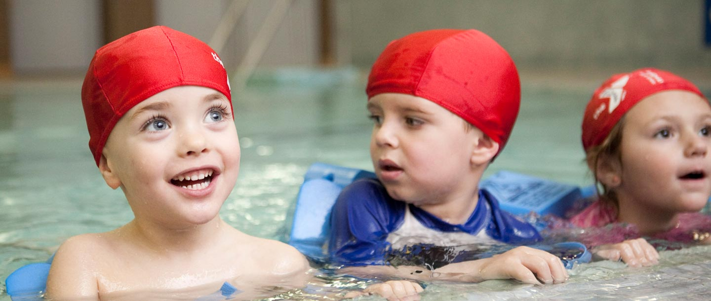 Preschool boys holding onto side of indoor YMCA pool during swim class