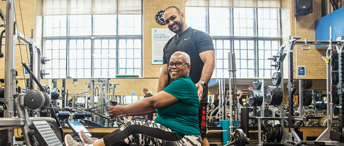 Woman working out in weight room of West Side YMCA with personal trainer