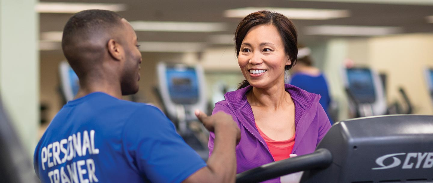 YUSA personal trainer talks to woman walking on treadmill