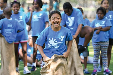 Summer camper jumping in sack during obstacle race at North Brooklyn YMCA