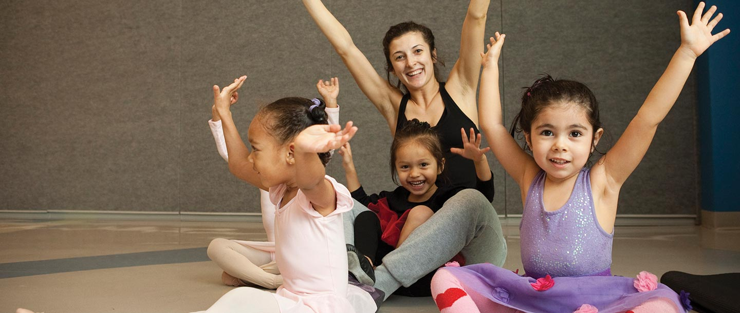 Three ballerinas sitting with YMCA instructor in studio class and arms up