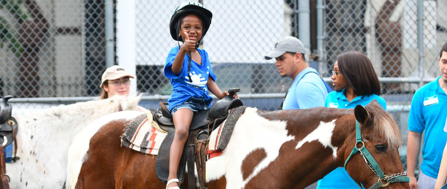 Summer camper gives thumbs up while riding horse at Dodge YMCA camp in Brooklyn