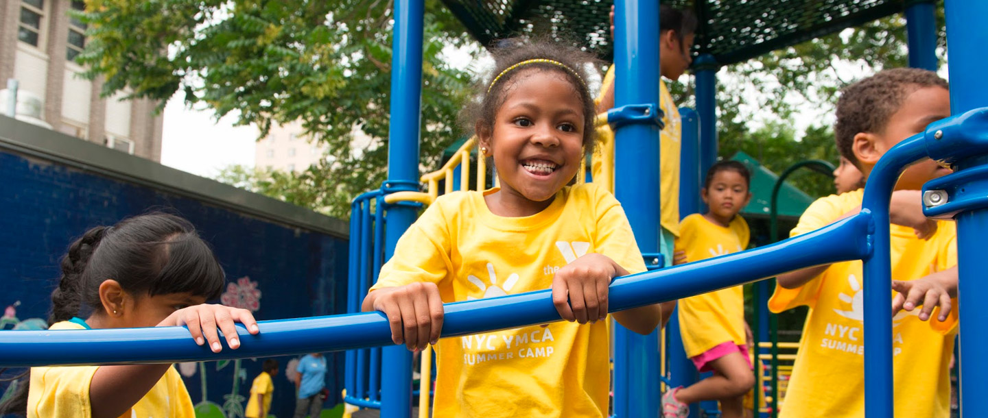Summer camper playing outside on playground during YMCA day camp in Brooklyn