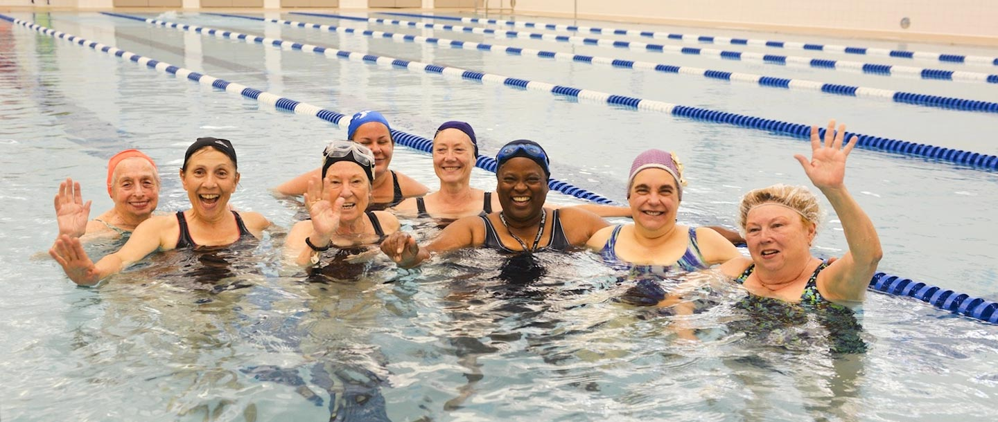 Group of women smiling at YMCA indoor pool water fitness class