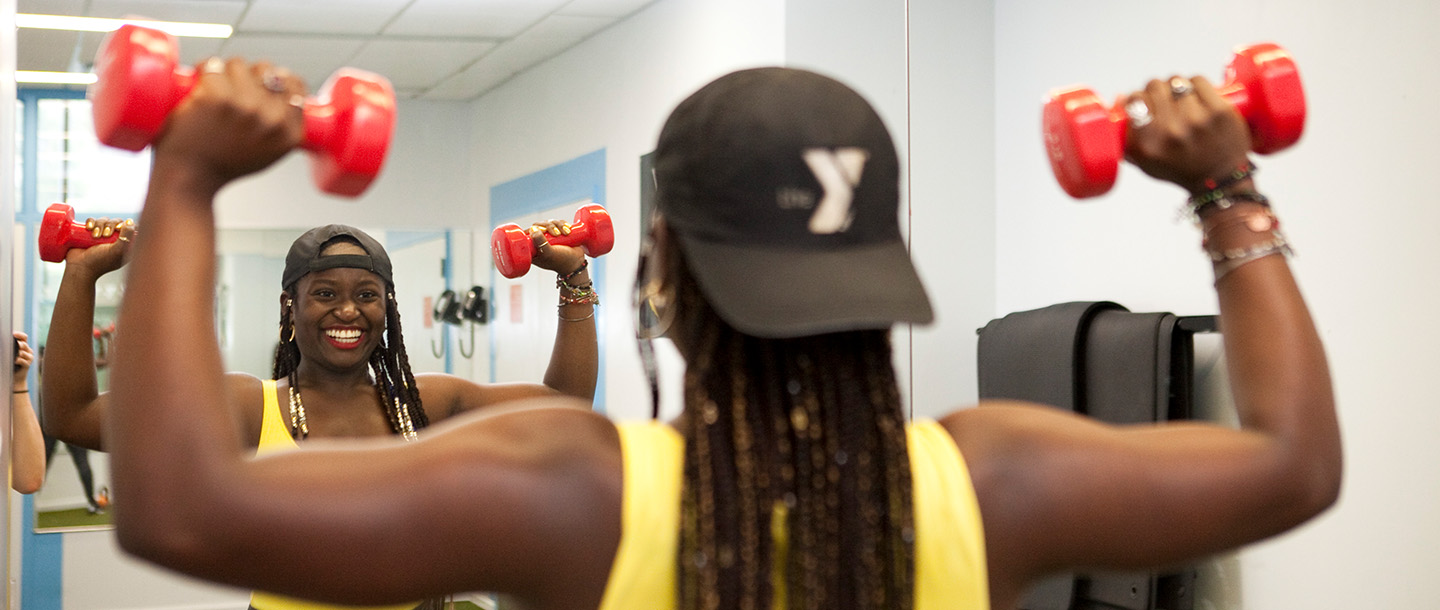 Woman holding weights with YMCA hat on