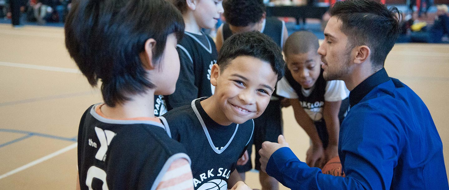 Boy smiling in group of basketball players at Park Slope Armory YMCA basketball league on indoor court