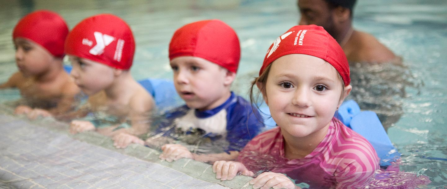 Preschoolers hold on to side of YMCA indoor pool during swim class