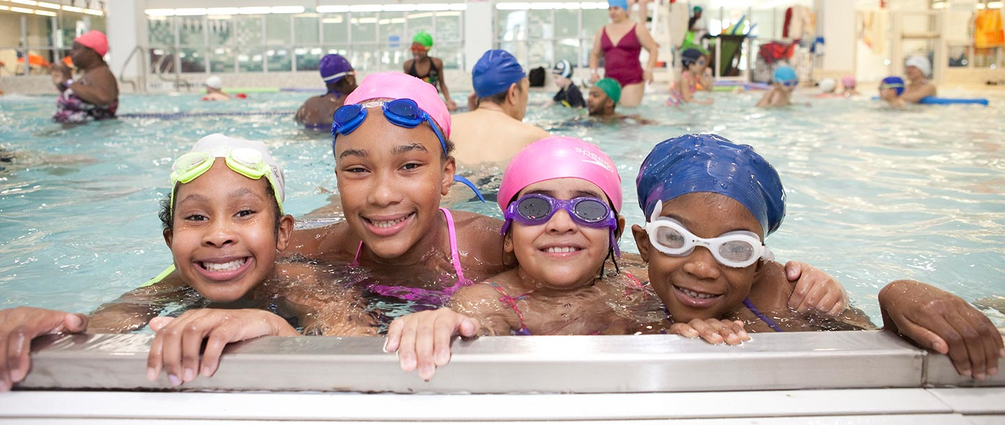 Four girls swimming at YMCA indoor pool in Brooklyn