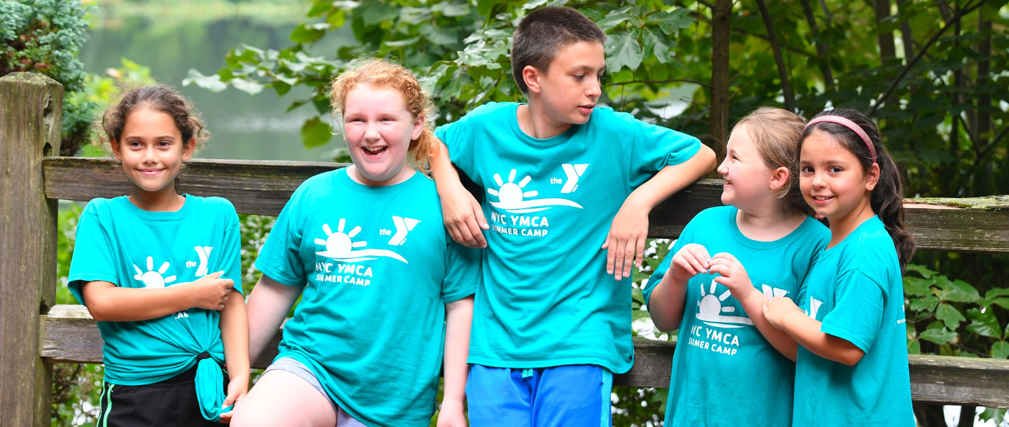 Group of summer campers laughing outside at Staten Island YMCA day camp