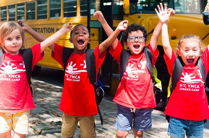 Four summer campers in front of school bus on YMCA camp field trip with Ridgewood Y in Queens.