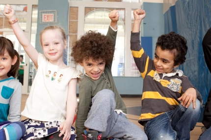 A diverse group of kids smile and raise their fists.
