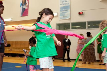 Girl does gymnastic skills during summer camp at YMCA in Manhattan