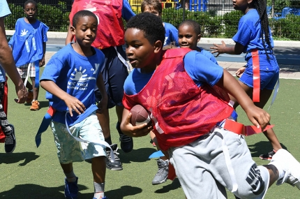 Campers at the YMCA playing flag football during youth sports