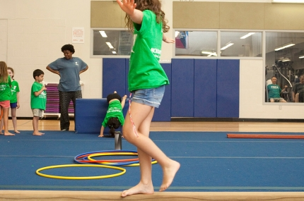 Kids learning gymnastics skills during youth sports class at the YMCA