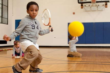 Kid learns tennis during youth sports class at the Harlem YMCA