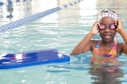 Girl learns swimming in pool at YMCA