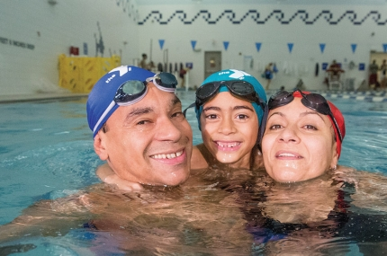 Family swimming in pool at YMCA