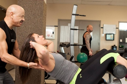 A personal trainer works with a woman in a gym.