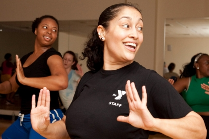A YMCA instructor leads a group fitness class.