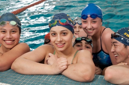 Group of Flushing Flyers swim team swimmers at indoor YMCA pool in Queens