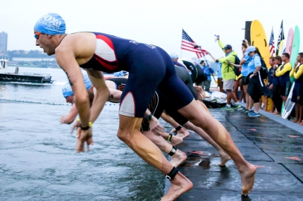 Swimmers dive into the water during the NYC triathlon.