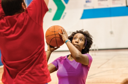 A woman shoots a basketball at the YMCA.