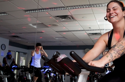 A woman instructor on a spin bike in the YMCA.