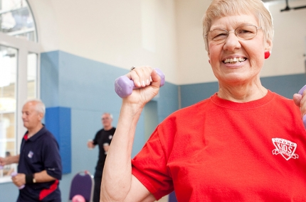 A senior lifts free weights in a YMCA fitness class.