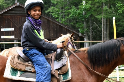 A child on a horse at the YMCA Sleepaway Camp.