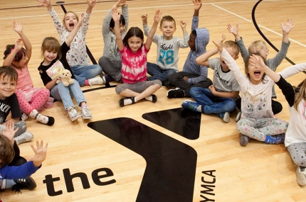 Kids sitting on the gymnasium floor around a YMCA logo.