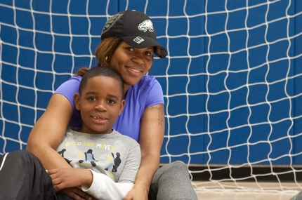 Mother and son play in gymnasium at YMCA