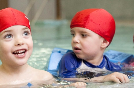 Three kids in swim caps learning to swim at the YMACA.