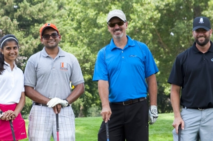 Four people in golf gear at a golf course.