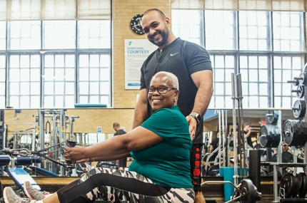 A woman works on strength training machine with a personal trainer at the YMCA.