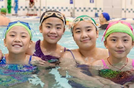 Four girls swimming in Coney Island YMCA indoor pool in Brooklyn