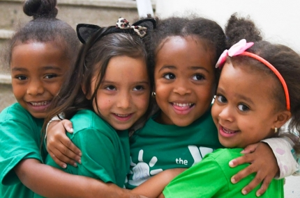 Four girls hugging and smiling at Harlem YMCA day camp in the summer
