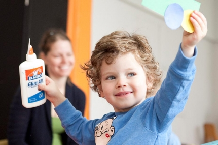Toddler holding glue and art project with arms up at the Prospect Park YMCA class