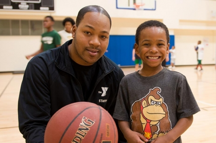 Young boy with basketball instructor at YMCA