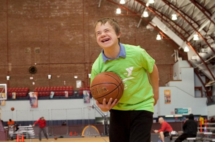 Boy in green t-shirt holding basketball at YMCA indoor gymnasium