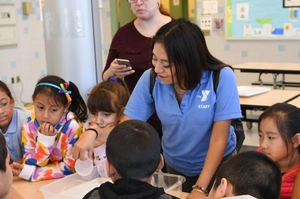 After school instructor helping children at YMCA program in Queens elementary school