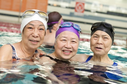 Three women smiling in indoor pool exercise class