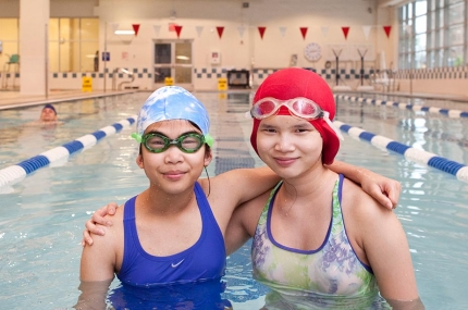 Two girls with swim caps and googles in lap lane of YMCA indoor pool
